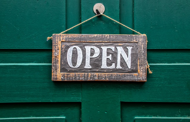 Sign hung on dark green front door stating 'Open'.