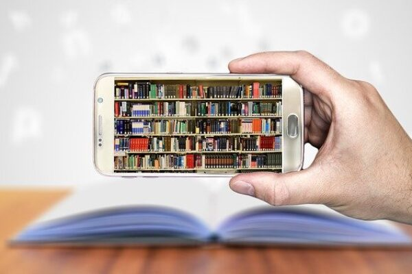 Mobile phone screen being held sideways to show a picture of  a bookcase full of books.